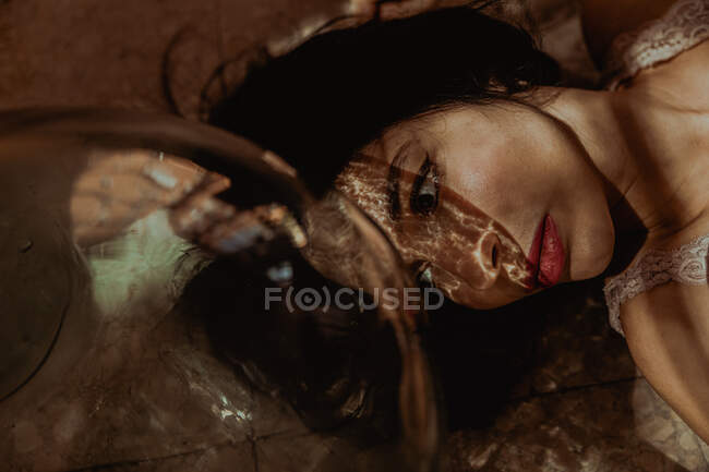 From above of gentle female in dress lying on floor near glass bottle in room with sunlight and looking away — Stock Photo