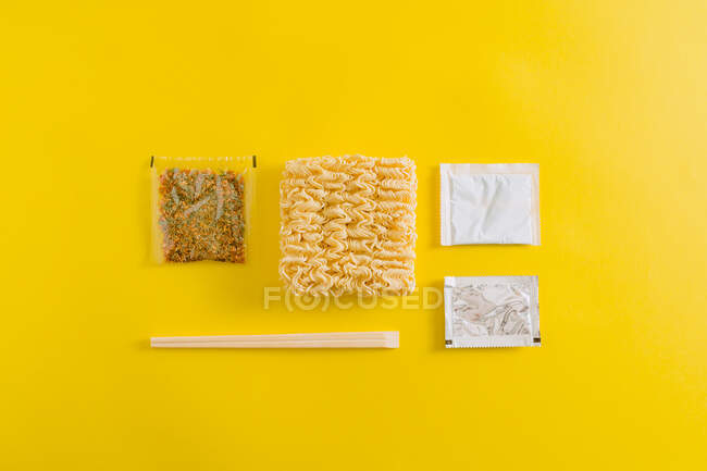 Top view layout of uncooked noodles with spices ingredients and sticks in plastic packages on yellow background — Stock Photo