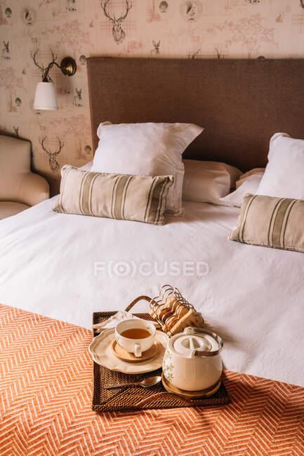 Зверху на піднос з вафлями з чаєм у чашці та чайкою, покладеними на м