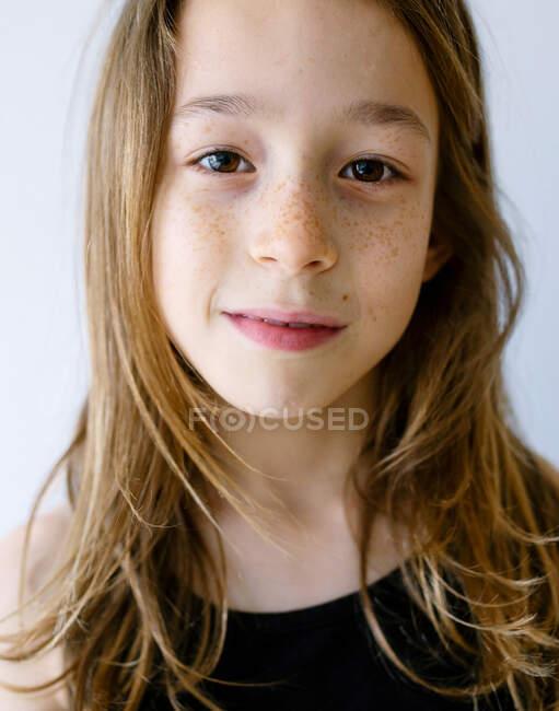 Восхитительная светловолосая девушка в майке смотрит в камеру и радостно смеется на белом фоне. — стоковое фото