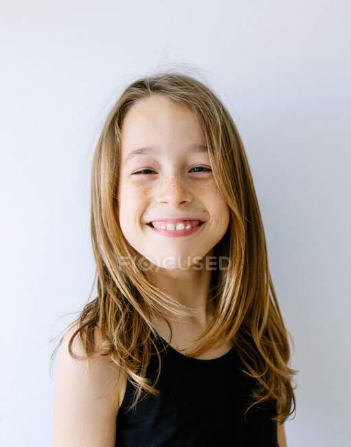 Allegro ragazza dai capelli biondi in maglietta guardando la fotocamera ridere felicemente contro lo sfondo bianco — Foto stock