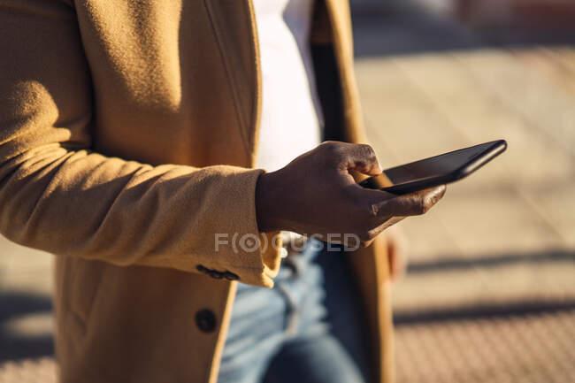 Colheita de anônimo jovem afro-americano masculino em roupa na moda na rua e navegação celular no dia ensolarado de verão — Fotografia de Stock