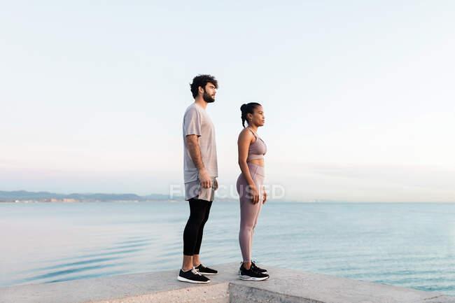 Вид сбоку спортсменки с мужчиной в спортивной одежде, созерцающей озеро — стоковое фото