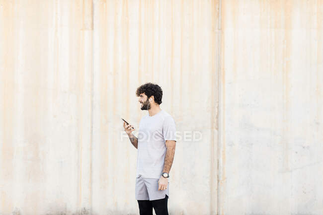 Young cheerful unshaven male athlete in sports clothes with cellphone looking forward in daytime during break from workout — Stock Photo