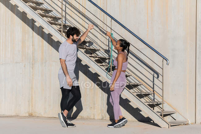 Side view of young sportsman with crossed legs speaking with smiling female partner in sportswear while looking at each other near staircase — Stock Photo