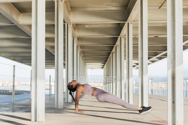 Вид сбоку молодой этнической спортсменки в спортивной одежде тренирующейся на дорожке под крышей при дневном свете — стоковое фото