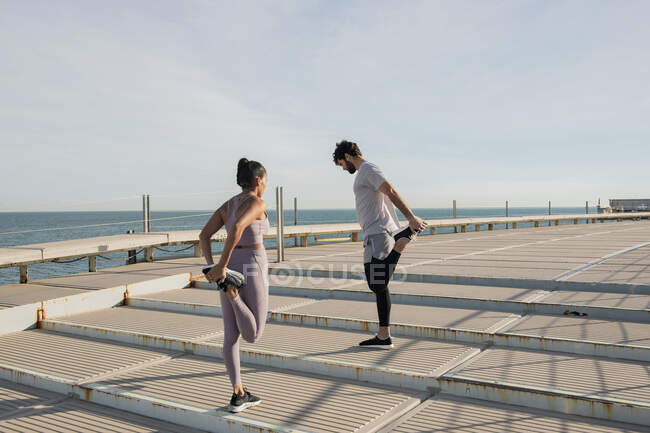 Unrecognizable multiethnic athletes in sportswear stretching legs during training on embankment staircase against ocean under cloudy sky — Stock Photo