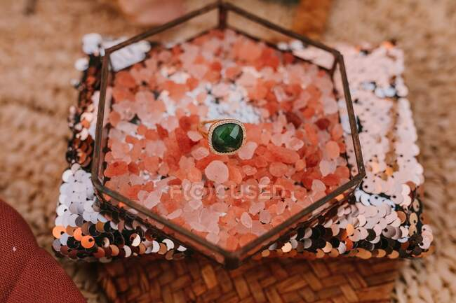 From above of gold ring with green gemstone placed in box with pink decoration placed on pillow with gold sequin during wedding celebration on blurred background — Stock Photo