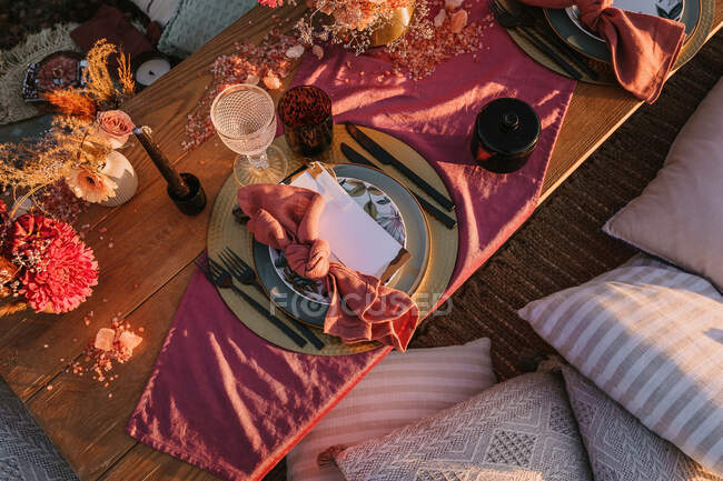 Top view of wooden table with envelope and napkin placed on plate near cutlery and colorful flowers on street in sunlight — Stock Photo