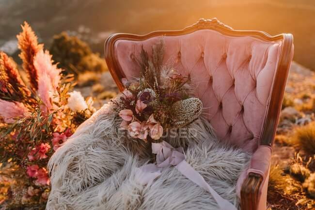 Розовое кресло с цветами на пушистой клетчатой клетке на винтажном ковре с декоративными перьями на вершине холма во время свадебного торжества — стоковое фото