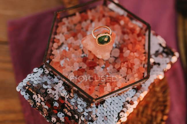 Сверху золотое кольцо с зеленым драгоценным камнем помещается в коробку с розовым декором помещается на подушку с золотой блесткой во время свадебного торжества на размытом фоне — стоковое фото