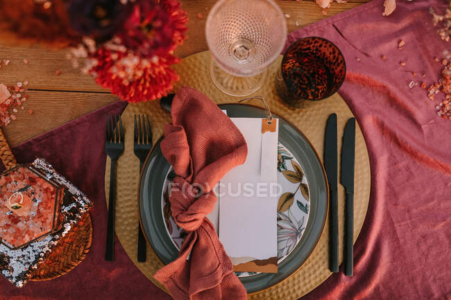 Top view of ornamental plate with colorful napkin with knot and white greeting card placed on table during wedding celebration — Stock Photo