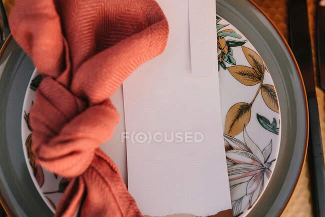 Верхний вид декоративной тарелки с красочной салфеткой с узлом и белой поздравительной открыткой на столе во время свадебного торжества — стоковое фото