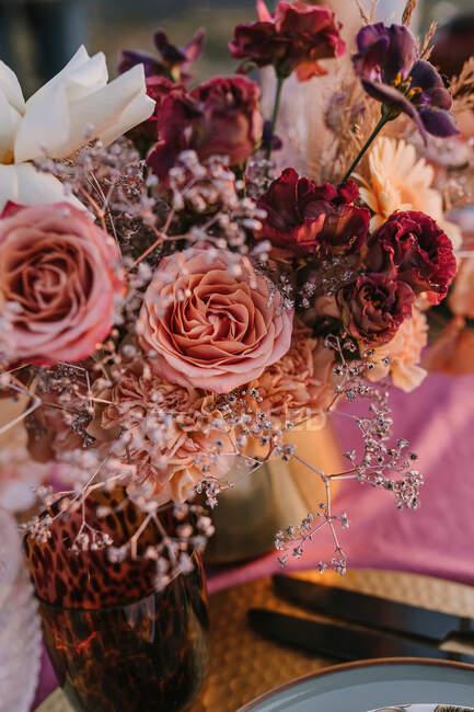 Bunte blühende Rosen mit zarten Blütenblättern in der Vase auf dem Tisch mit Teller und Besteck bei der Hochzeitsfeier auf der Straße — Stockfoto