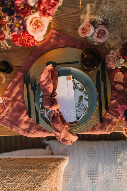 Vista dall'alto del piatto ornamentale con tovagliolo colorato con nodo e biglietto di auguri bianco posto sul tavolo decorato durante la celebrazione del matrimonio — Foto stock