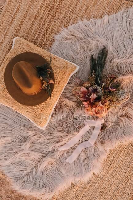 Вид сверху на трехцветную шляпу на подушке, размещенную рядом с декоративными элементами с цветами на пушистых идолах на улице во время свадьбы — стоковое фото