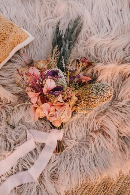 Из выше расположение свежих розовых цветов с растениями и декоративной ветви помещены на мягкой клетке с лентой во время празднования свадьбы — стоковое фото