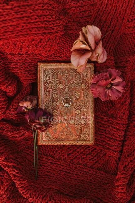 Draufsicht des Eherings auf Buch in der Nähe Knospen von bunten Blumen auf rotem Strickstoff während der Hochzeitsfeier platziert — Stockfoto