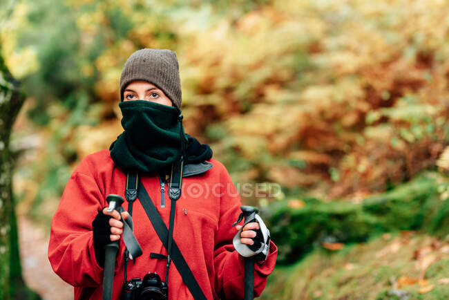 Young female hiker in warm clothes with photo camera on neck practicing Nordic walk in autumn forest and looking away dreamily — Stock Photo