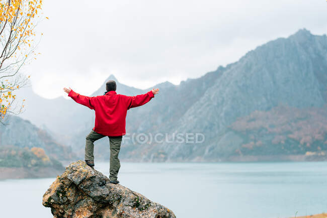 Back view anonymous traveler in warm clothes standing with arms outstretched on massive rock and admiring scenic mountain range surrounding tranquil lake on autumn day — Stock Photo