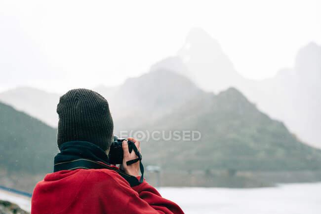 Indietro vista anonimo viaggiatore in capispalla in piedi su roccia massiccia e scattare foto mentre ammirando cresta di montagna nebbioso che circonda lago calmo il giorno d'autunno — Foto stock