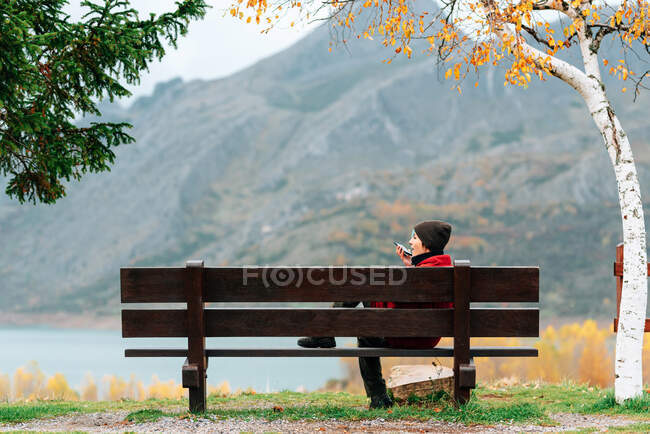 Side view woman in outerwear resting on bench in picturesque autumn park against severe mountain range and calm lake and talking phone — Stock Photo