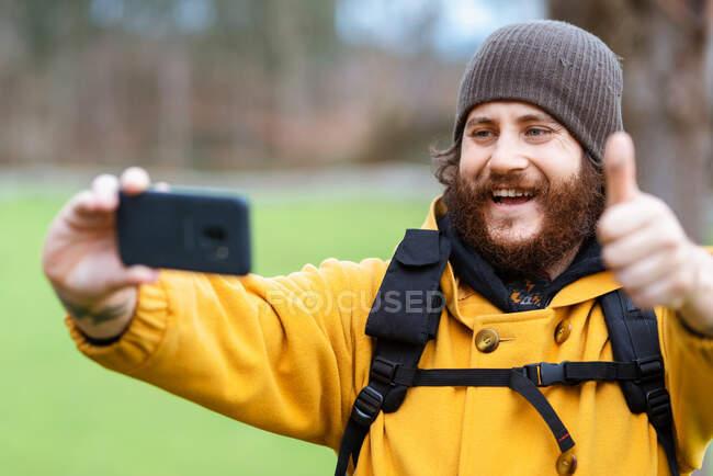 Heureux adulte barbu voyageur masculin avec pouce vers le haut en prenant autoportrait sur téléphone portable en plein jour — Photo de stock