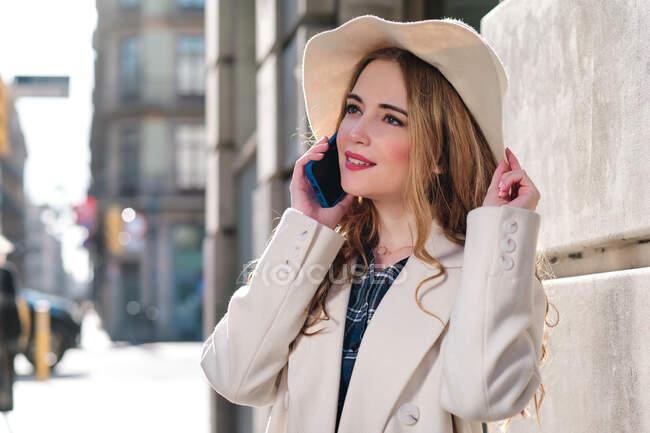 Giovane donna affascinante in cappello che parla al cellulare mentre distoglie lo sguardo in città nella giornata di sole — Foto stock
