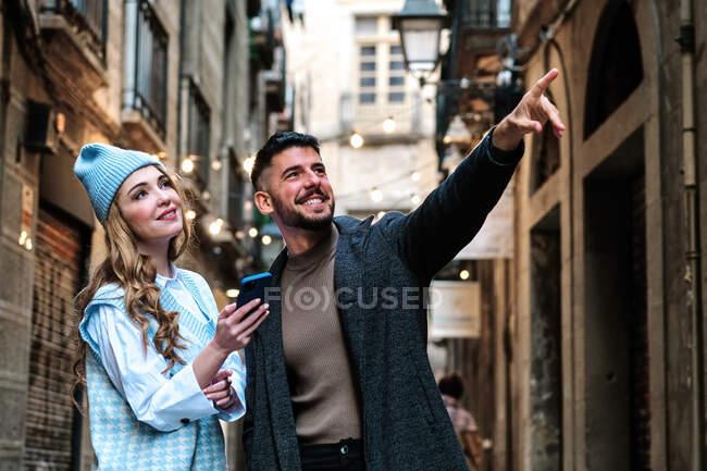 Молодая мечтательная туристка с сотовым телефоном рядом с контентом бородатый парень указывая пальцем, глядя вверх в городе — стоковое фото