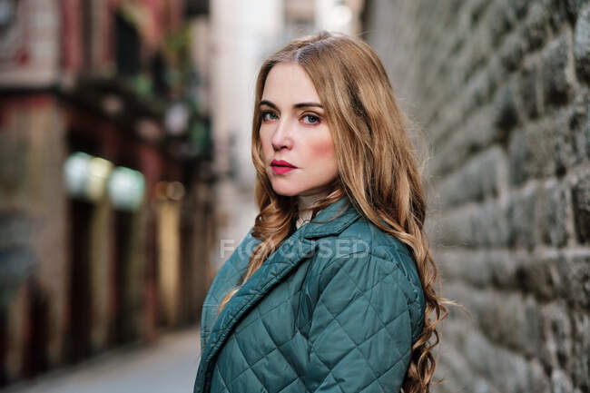Young serious woman in green coat looking at camera on city street in daylight — Stock Photo