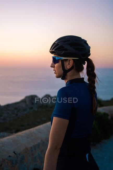 Задумлива самиця в спортивному лаві з шоломом стоїть з велосипедом на порожній дорозі в величних горах. — стокове фото