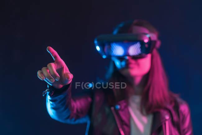 Нерозпізнавана жінка з витягнутою рукою, одягнена в VR навушники під час вивчення віртуальної реальності під синім неоновим світлом. — стокове фото