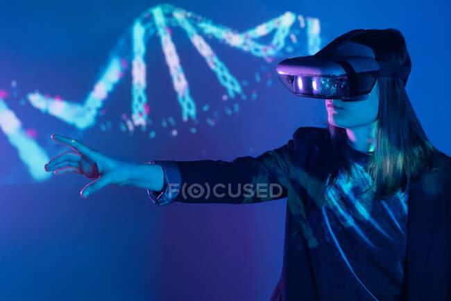 Vista lateral de una hembra irreconocible con el brazo extendido con auriculares VR mientras explora la realidad virtual bajo la luz de neón azul cerca de la pared con iluminación del proyector - foto de stock