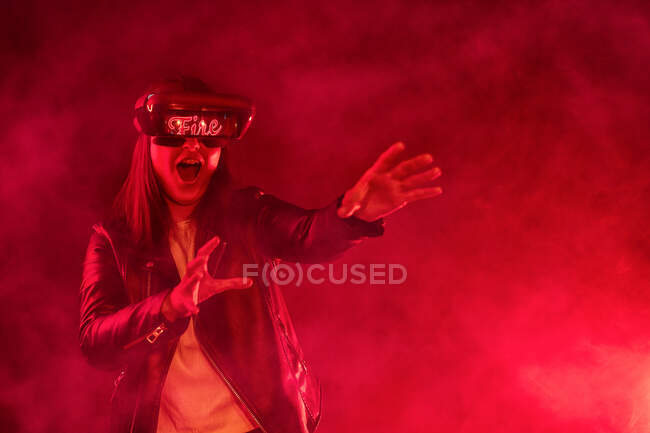 Terrified anonymous female with outstretched arms wearing modern headset screaming while exploring cyberspace in room with red neon light and smoke — Stock Photo