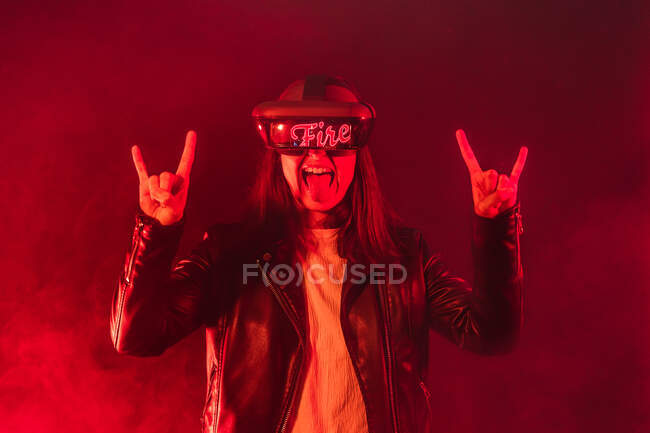 Expressive anonymous female wearing VR goggles with Fire word making horn sign while standing in red neon light with smoke — Stock Photo