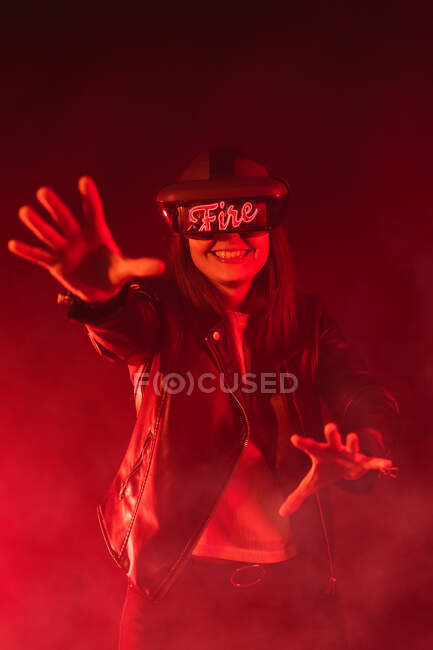 Anonymous female with outstretched arms wearing modern headset screaming while exploring cyberspace in room with red neon light and smoke — Stock Photo