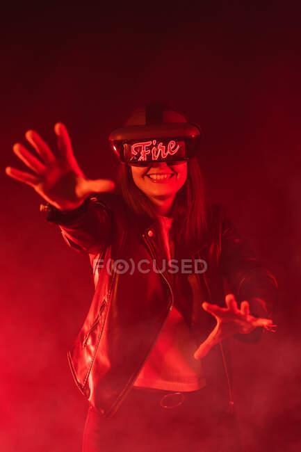 Анонімні жінки з витягнутими руками, одягнені в сучасні голосні крики, під час вивчення кіберпростору в кімнаті з червоним неоновим світлом і димом. — стокове фото