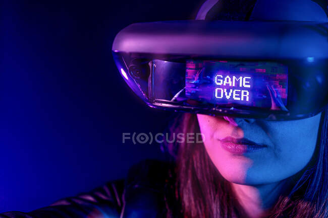 Unrecognizable female wearing modern headset with Game Over inscription while exploring virtual reality in dark room with neon light near wall — Stock Photo