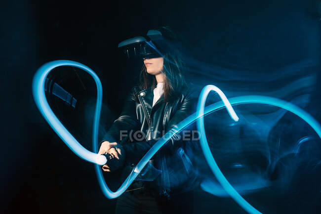 Side view of unrecognizable female wearing modern VR headset and playing with motion game controller in blue neon lights while exploring cyberspace — Stock Photo