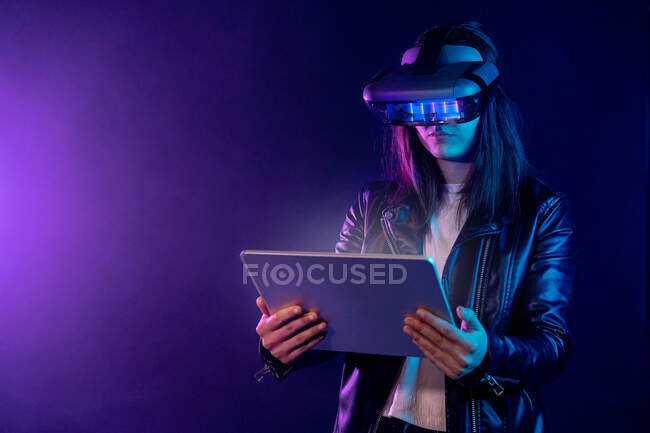 Concentrated anonymous female wearing modern VR headset standing near wall in dark room with contemporary tablet in hands under neon illumination — Stock Photo