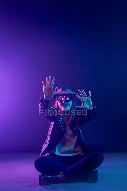 Unrecognizable female with outstretched arm wearing VR headset while exploring virtual reality under blue neon light and sitting on floor — Stock Photo