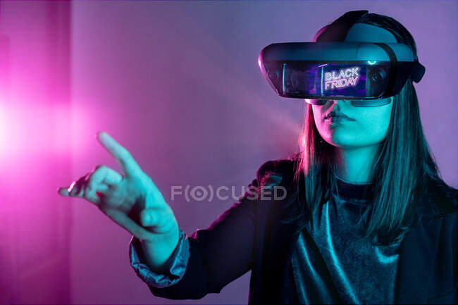 Unrecognizable female wearing VR headset while exploring virtual reality under blue neon light — Stock Photo