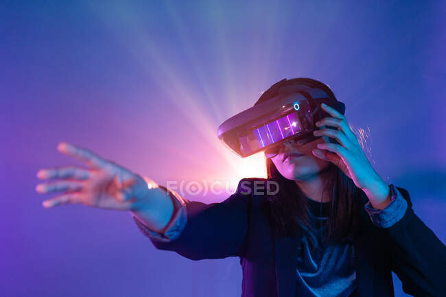 Unrecognizable female with outstretched arm wearing VR headset while exploring virtual reality under blue neon light — Stock Photo