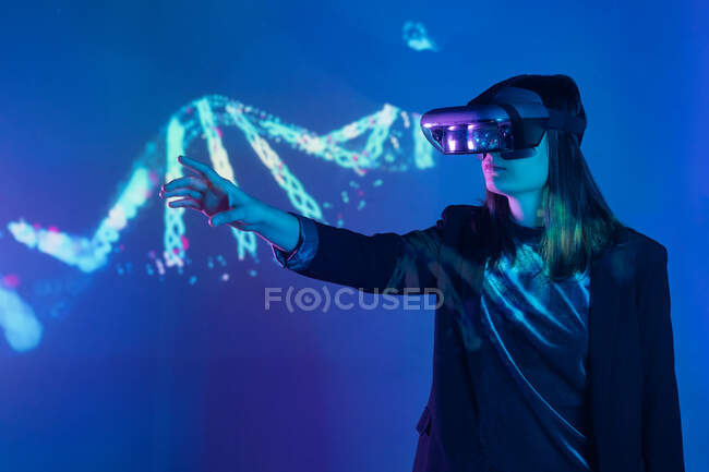 Side view of unrecognizable female with outstretched arm wearing VR headset while exploring virtual reality under blue neon light near wall with projector illumination — Stock Photo