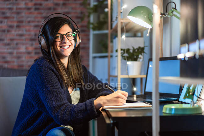 Side view of cheerful female composer in headphones taking notes in notebook while sitting at table with laptop during remote work from home — Stock Photo