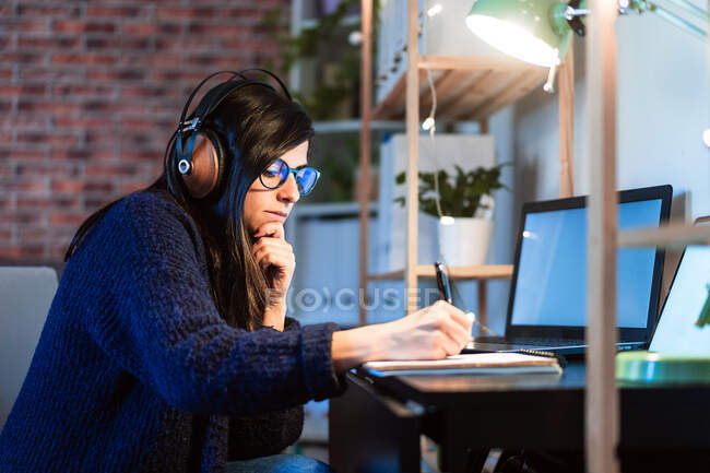 Side view of concentrated female composer in headphones taking notes in notebook while sitting at table with laptop during remote work from home — Stock Photo