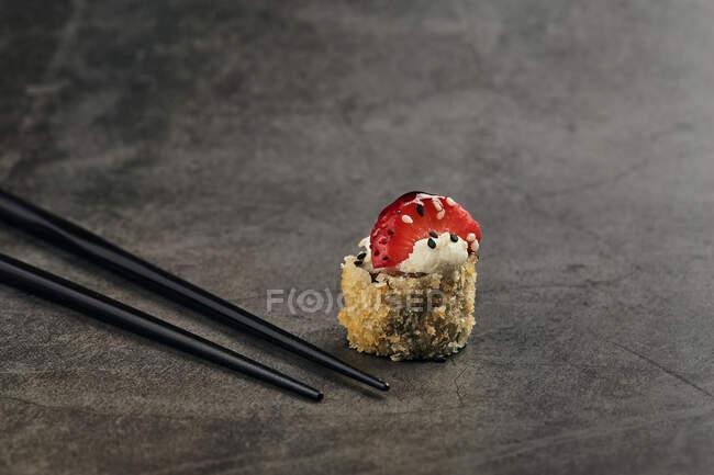 Hoher Winkel der gebratenen japanischen Sushi-Rolle mit Sesam- und Erdbeerscheibe in der Nähe von Bambusstäben — Stockfoto