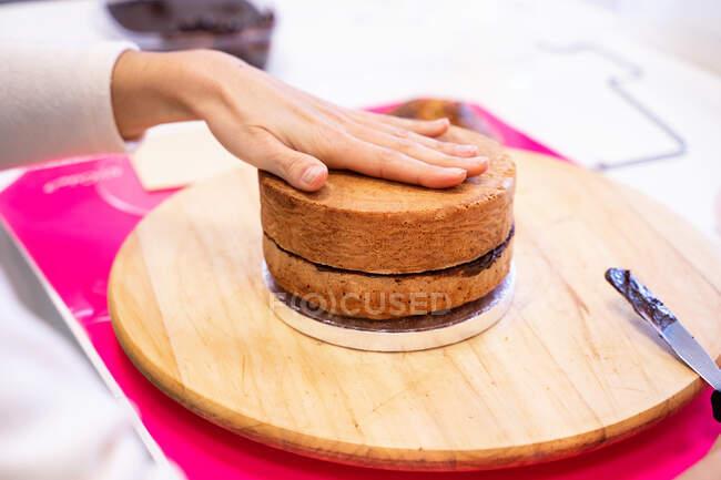 Нерозбірлива людина натискає руку на торт на дерев