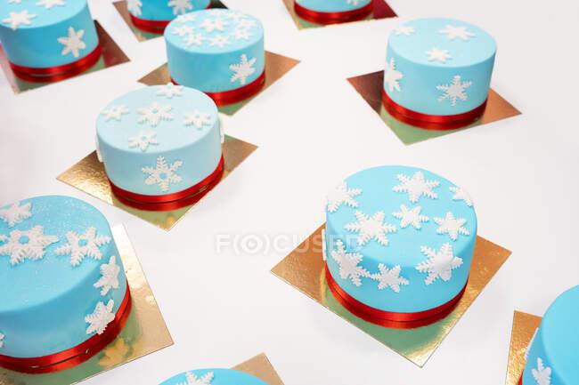 Високий кут різних смачних зимових тістечок з їстівними сніжинками на золотих елементах пекарні. — стокове фото