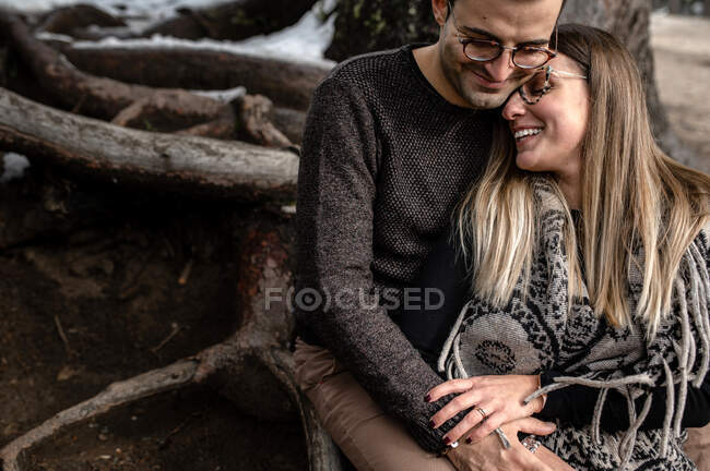 Full body of positive gentle couple sitting near tree and hugging each other during romantic day in woods — Stock Photo